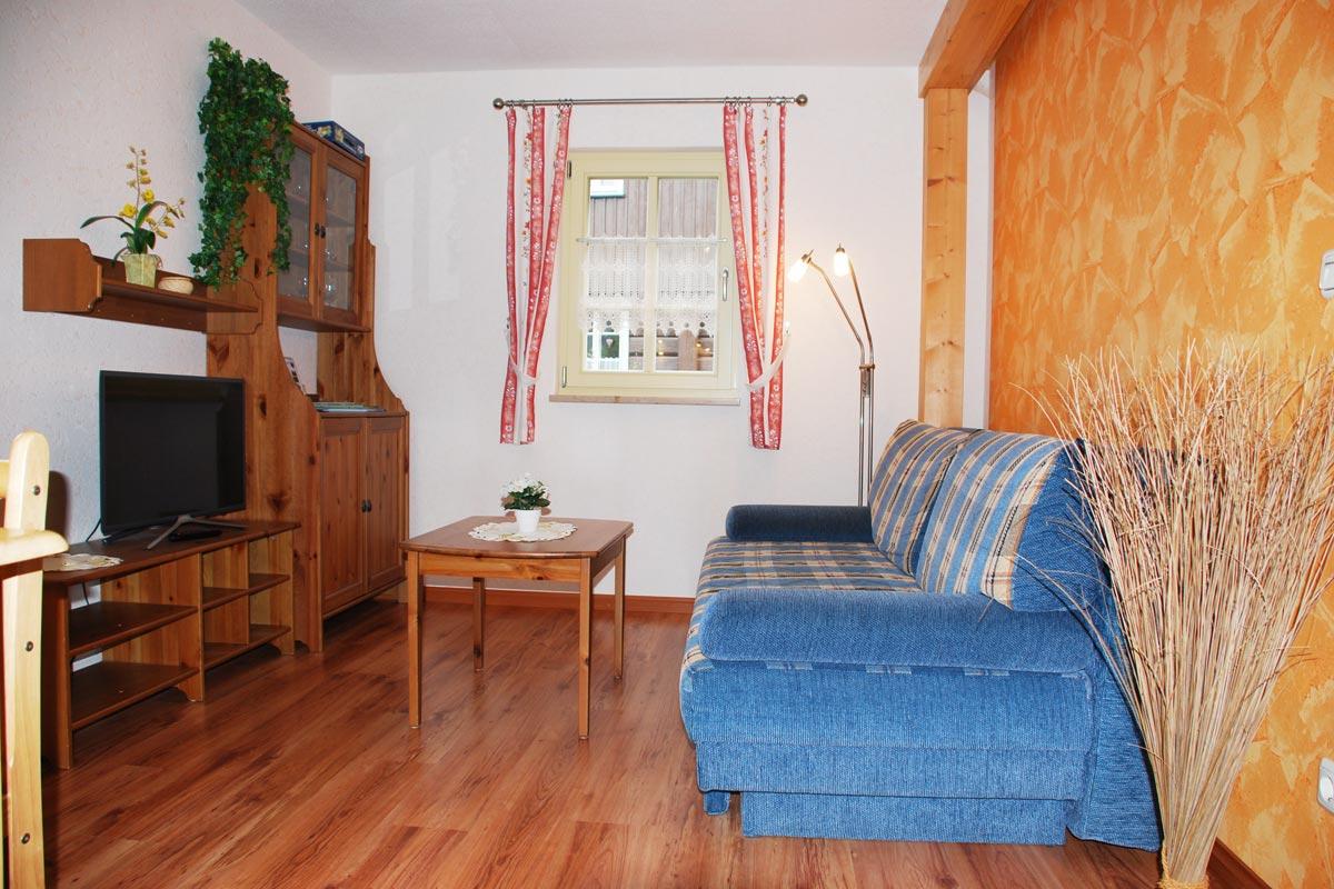 Ferienhaus am Osterbrunnen - Ferienwohnung 1 und 2 - Wohnbereich mit Sofa und TV