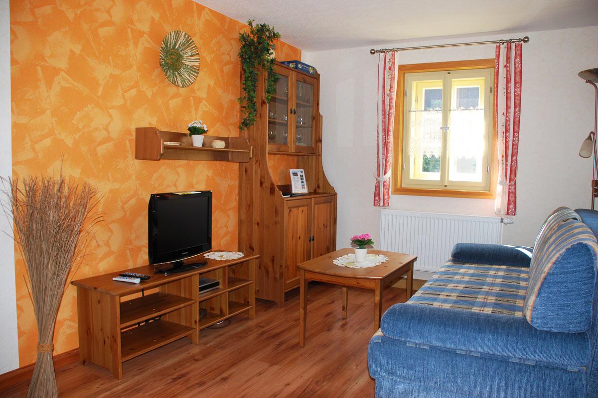 Ferienhaus am Osterbrunnen - Ferienwohnung 3 - Wohnzimmer mit Sofa und TV