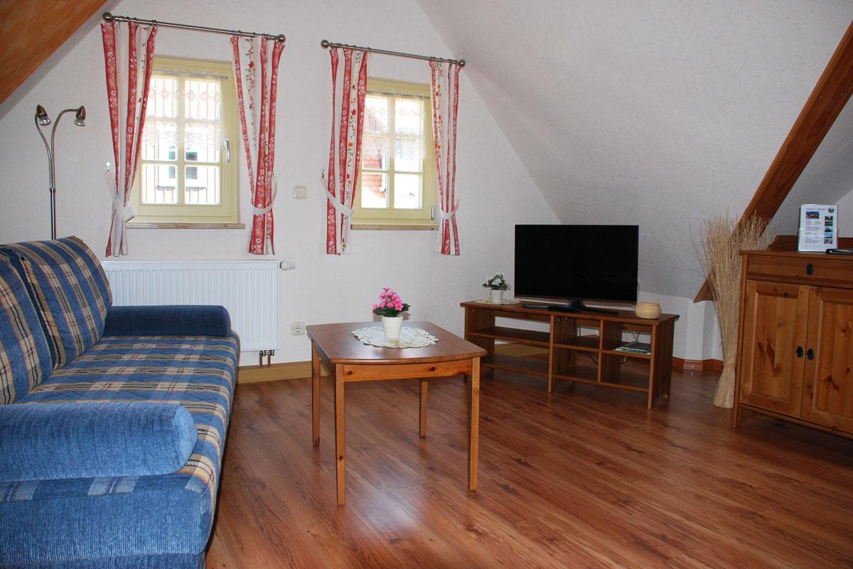 Ferienhaus am Osterbrunnen - Ferienwohnung 4 - Wohnzimmer mit Sofa und TV